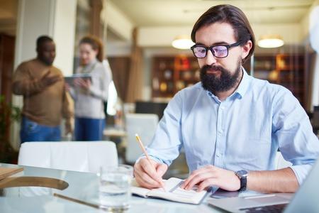 hombre escribiendo: Escritura empleado moderno plan de trabajo en el bloc de notas