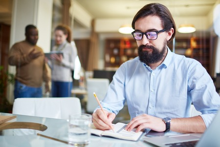 busy beard: Modern employee writing working plan in notepad