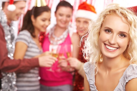 Blond girl looking at camera with toothy smile on background of toasting friends photo