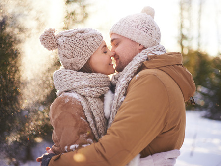 adult couple: Young amorous couple in winterwear going to kiss