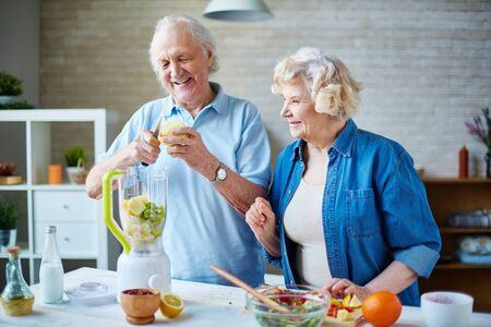 retirement happy man: Senior man and his wife going to make smoothie from fresh fruits Stock Photo