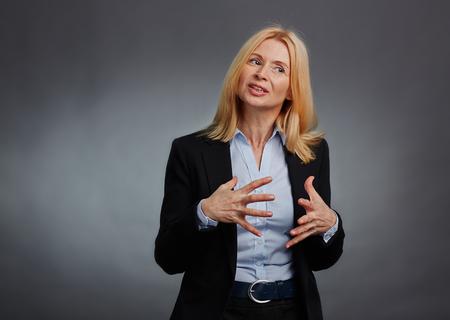 explaining: Mature employee in suit gesticulating while explaining something