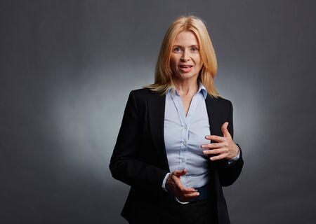 explaining: Mature businesswoman looking at camera while explaining something