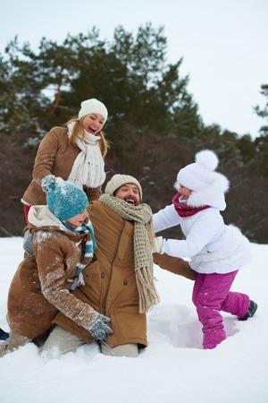 snowdrift: Cheerful kids and parents having fun in snowdrift