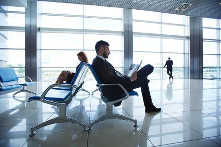personas leyendo: Gente de negocios sentado en el aeropuerto a la espera de la salida Foto de archivo