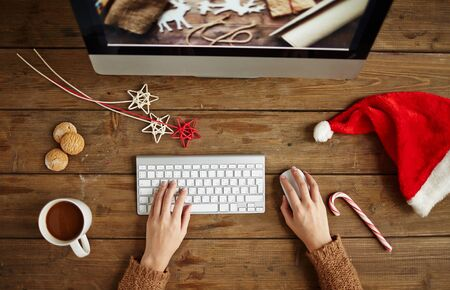 designer: Female designer working in front of pc with coffee, biscuits and Christmas symbols near by