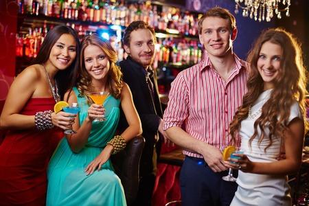 jovenes tomando alcohol: Hermosas gente bebiendo c�cteles en la discoteca Foto de archivo