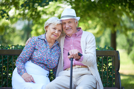 Pares mayores románticos relajado en el banco del parque