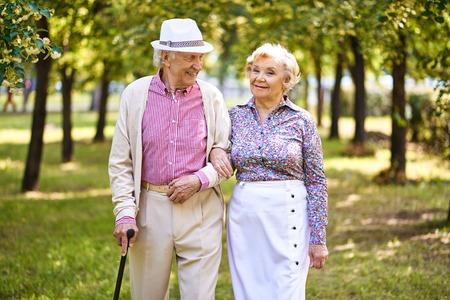 persona mayor: Mayores felices caminando juntos en el parque
