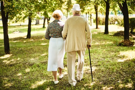 Happy seniors taking a walk in the park on sunny day Stock Photo
