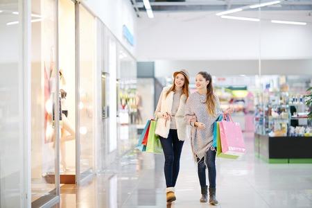 mujer elegante: Las mujeres j�venes con bolsas de papel para caminar en el centro comercial