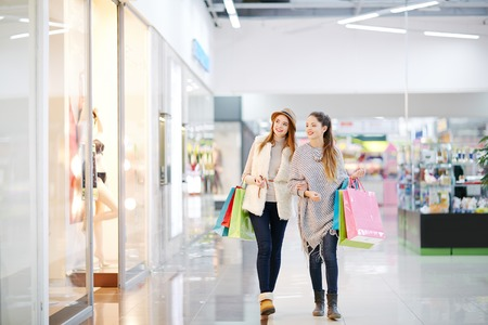 elegant woman: Young women with paper bags walking in the mall