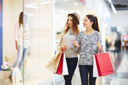 mujeres elegantes: Dos mujeres elegantes se ven en la tienda de ropa escaparate Foto de archivo