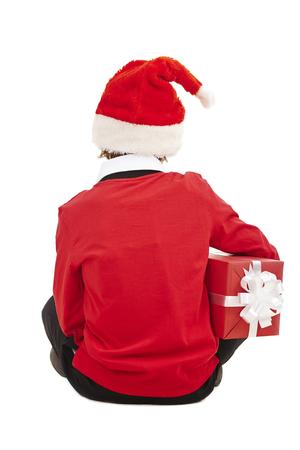 Rear view of boy in Santa cap holding gift-box photo