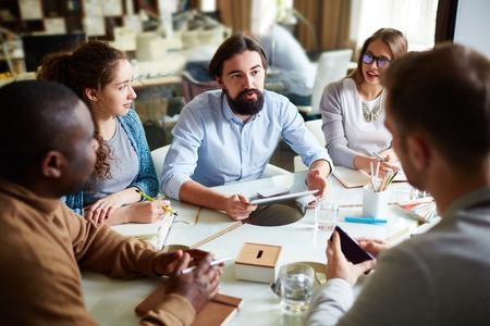 reunion de personas: Grupo de trabajadores de oficina escuchando colega en reuni�n Foto de archivo