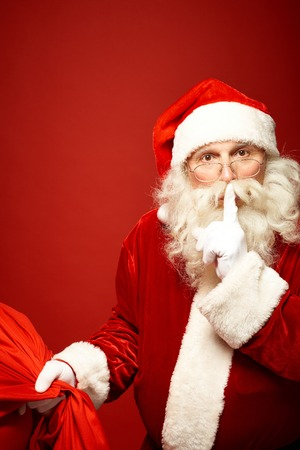 口の中で人差し指を維持するクリスマス プレゼントの袋とサンタ クロース