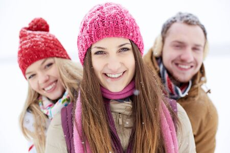 winterwear: Happy friends in winterwear looking at camera during snowfall Stock Photo