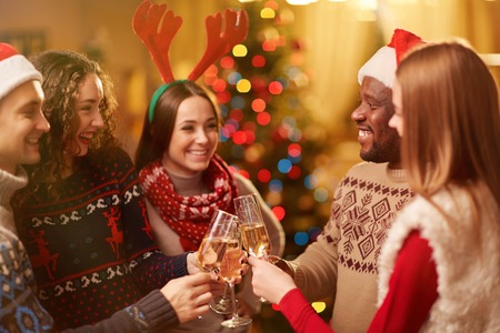 liquor girl: Happy friends toasting with bubbly champagne on Christmas eve