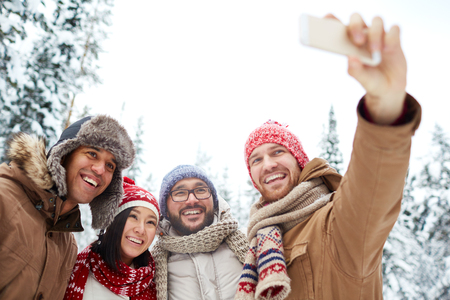 winterwear: Young friends in winterwear making selfie in natural environment