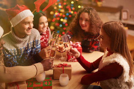 party friends: Happy young friends with flutes of champagne toasting on Christmas home party
