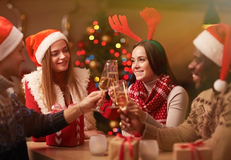 liquor girl: Happy young friends with champagne celebrating Christmas