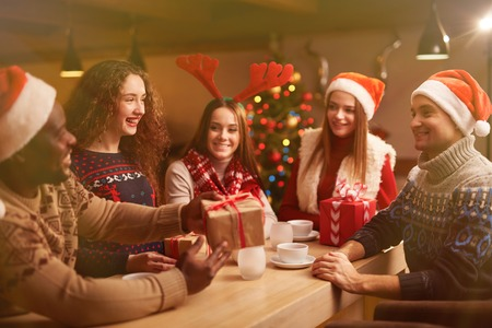 congratulating: Happy young friends congratulating each other on Christmas evening Stock Photo