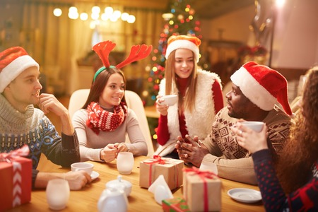 christmas tea: Friendly guys and girls talking while having tea on Christmas evening