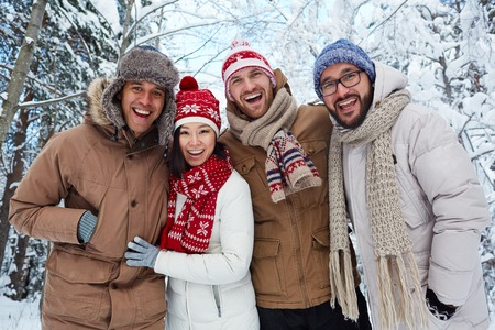 winterwear: Young multi-ethnic friends in winterwear looking at camera outdoors