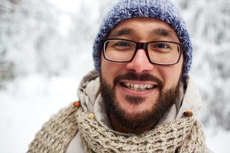 winterwear: Happy Asian guy in winterwear looking at camera outside