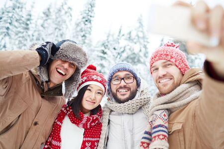 winterwear: Happy friends in winterwear making selfie in park Stock Photo