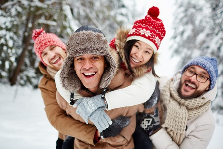 group of young people: Ecstatic friends having fun in winter park Stock Photo