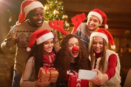 Amigos alegres que hacen selfie en la noche de Navidad