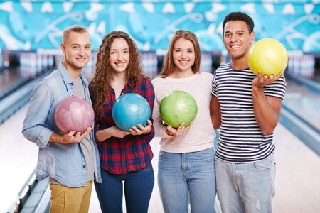 four friends: Group of four friends holding bowling balls and smiling Stock Photo