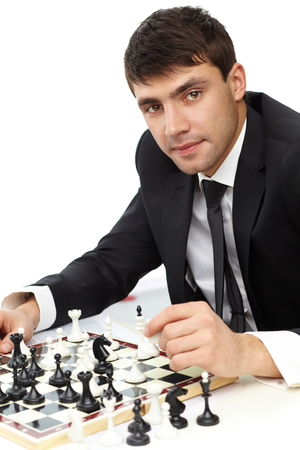 Young businessman playing chess solo on white background photo