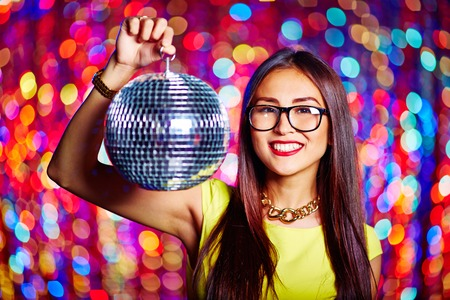 clubber: Beautiful young woman holding disco ball and smiling