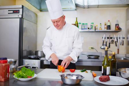 cuchillo de cocina: Cocine cortar verduras en la tabla de cortar Foto de archivo