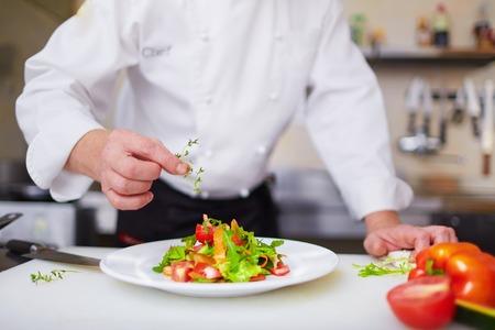 Cocinero de sexo masculino adornando el plato en la cocina Foto de archivo
