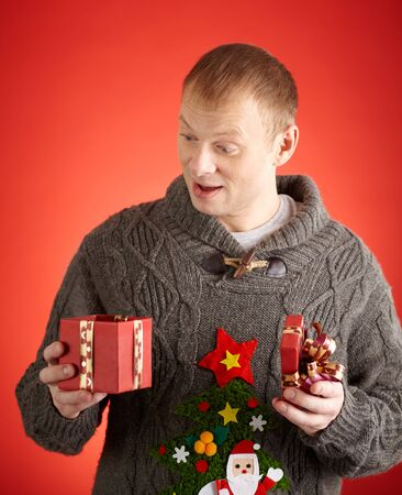 unpacked: Surprised man looking into open gift-box in his hands