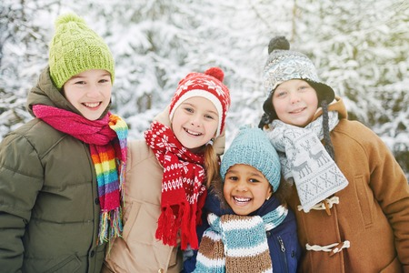 natural looking: Friendly kids in winterwear looking at camera in natural environment in winter