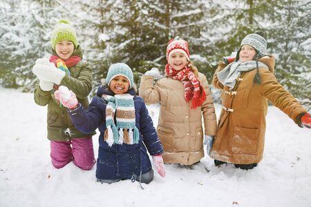 palle di neve: Cute piccoli amici che giocano a palle di neve in inverno parco