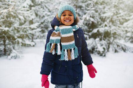natural looking: Joyful kid in winterwear looking at camera in natural environment in winter