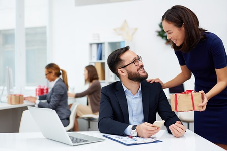 corporates: Happy businesswoman giving Christmas present to colleague Stock Photo