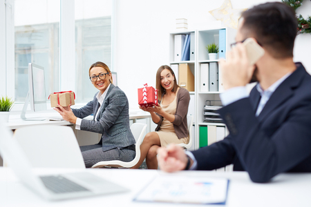 Happy businesswomen showing Christmas gifts to colleague in office