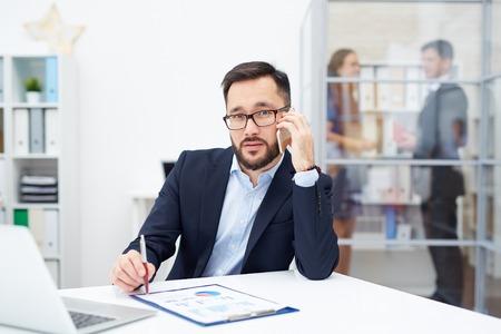 hombres guapos: Empleador hermoso que llama en lugar de trabajo en la oficina Foto de archivo