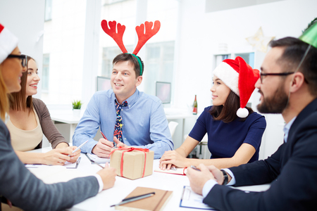 Group of business people in Santa caps and with deer horns interacting at meeting on Christmas day Stock Photo