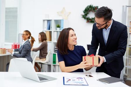 Mladý podnikatel dává jeho kolega vánoční dárek v kanceláři Reklamní fotografie