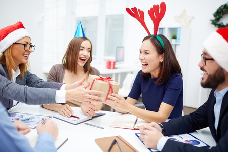 Cheerful business people giving Christmas presents during meeting