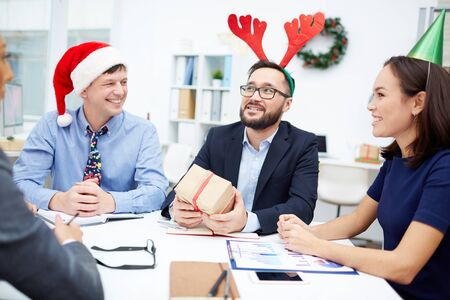 and guessing: Businessman with red deer horns guessing what gift-box contains among his colleagues in office Stock Photo