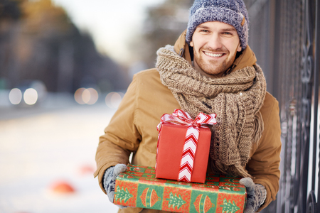 Young man with Christmas gifts looking at camera outside