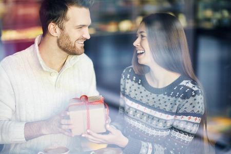 Chico amoroso y niña felicitando unos a otros en Día de San Valentín en el café
